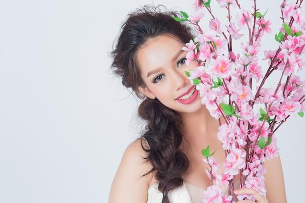 Красивое азиатское платье свадьбы изделий женщины держа букет с copyspace. процесс для винтажного цвета пленки