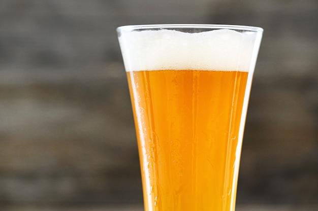 Copyspaceとウッドの背景にガラスのビールのクローズアップ。