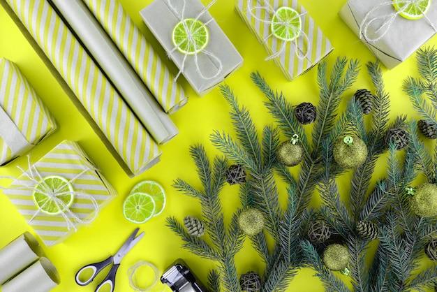 パッケージ化されたクリスマスプレゼントの準備。黄色の背景に箱、包装紙、はさみ。トップビュー、copyspace。