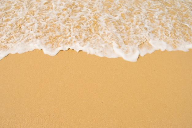 砂浜で青い海の柔らかい波。 copyspaceの背景