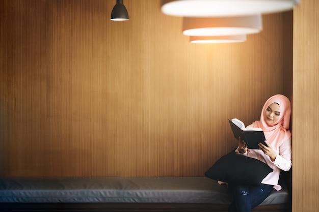 Красивая молодая мусульманская женщина читая книгу перед деревянной стеной с copyspace.
