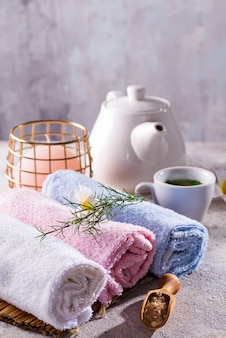 花、塩のスプーン、竹のマット、バススパトリートメント、石のテーブル、緑茶のcopyspaceとカラータオル