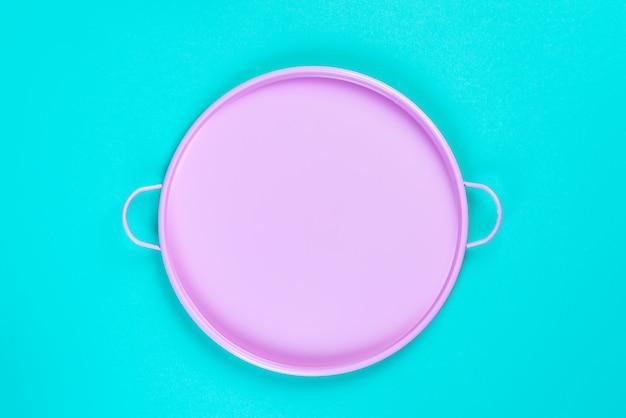 青い紙の背景、デザイン、フレームのcopyspaceの上面にピンクのブリキの円トレイ。静物構成。