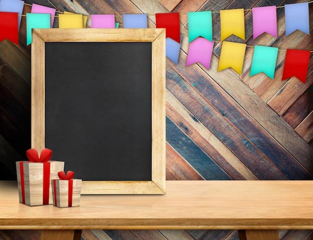 ギフト用の箱と斜めの木製の壁で木の上のカラフルなフラグを持つ空の黒板。 copyspace