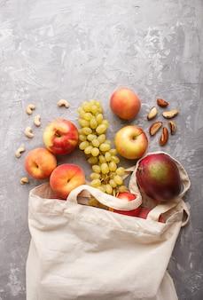 Плоды в многоразовой хлопчатобумажной текстильной белой сумке на сером бетоне. ноль отходов, покупка, хранение и переработка. вид сверху, плоская планировка, copyspace.