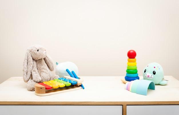 Copyspaceと木製のテーブルの壁のおもちゃのカラフルな子供のおもちゃの