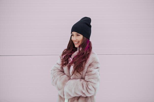 カラフルなピンクの壁にミンクのコートでかなり笑顔の女性のファッションの肖像画。 copyspace