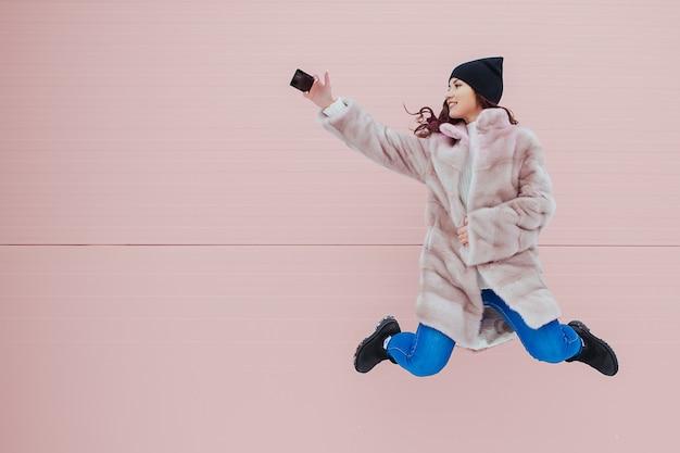 カラフルなピンクの壁にスマートフォンでミンクのコートでかなり笑顔とジャンプの女性のファッションの肖像画。 copyspace。