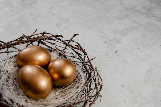 Золотые пасхальные яйца в гнезде птиц на деревенском фоне. праздник пасхи концепции абстрактный фон copyspace вид сверху несколько объектов.