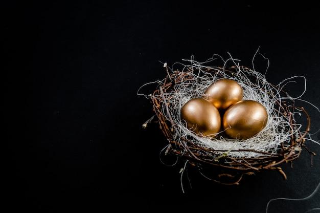 鳥の黄金のイースターエッグ黒の背景に巣します。イースター休暇の概念抽象的な背景copyspaceトップビューいくつかのオブジェクト。