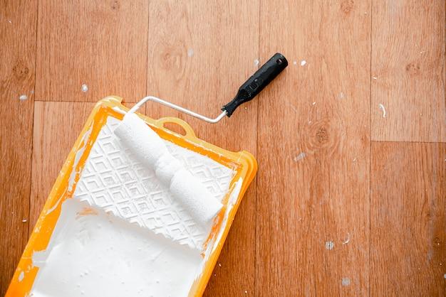 黄色のボックスに白いペンキでペイントローラー。水平ビューcopyspace。家の修理の概念