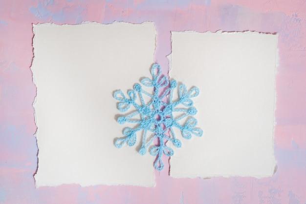 クリスマスの背景に空白のノートブック、青かぎ針編みスノーフレーク、紫ピンクの背景に手作り。破れた紙の傾向。フラット横たわっていた、トップビュー。 copyspace。