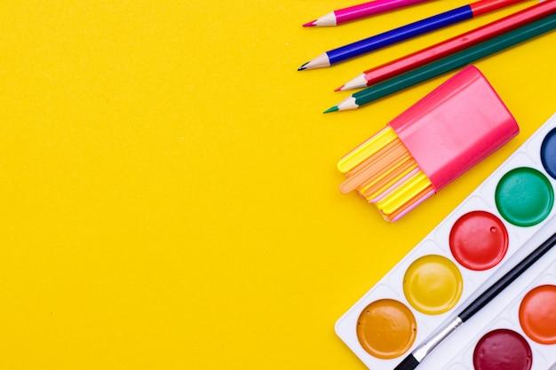 黄色の背景に事務用品。 copyspaceと明るい黄色のテーブルにさまざまな学用品