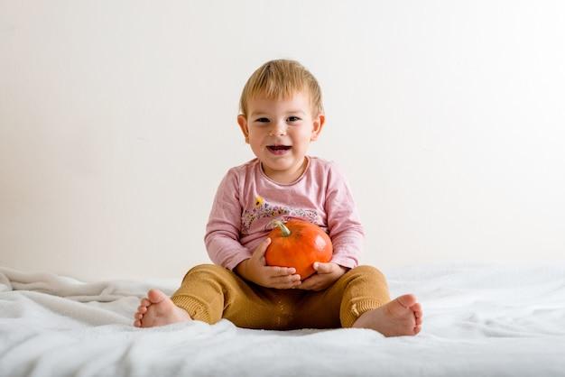 Милая маленькая девочка обнимая тыкву на кровати внутри помещения. copyspace