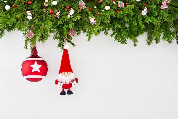 クリスマスの背景。白い木製の背景にサンタとクリスマスのモミの木の枝。 copyspace、トップビュー