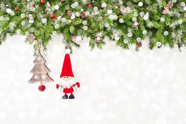 白い木製の背景にサンタとクリスマスのモミの木の枝を装飾されています。 copyspace、トップビュー