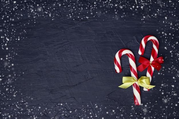 クリスマスの背景。クリスマスツリーとキャンディー杖とクリスマスのグリーティングカード。 copyspace、暗い背景