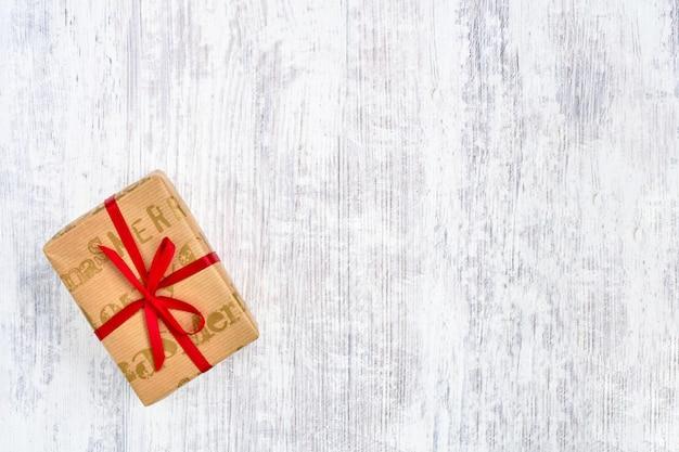 白い木製のテーブルに赤いリボンで飾られた紙に包まれたギフトボックス。トップビュー、copyspace