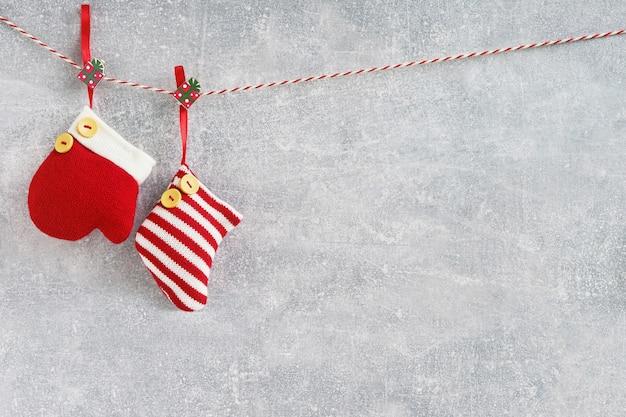 クリスマスの背景。赤いクリスマスソックスと灰色の背景にミトン。 copyspace。