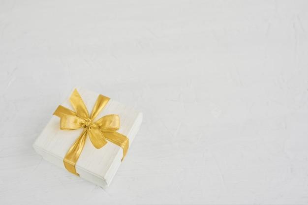白い背景の上の黄金のリボンで飾られたギフトまたはプレゼントボックス。トップビュー、copyspace。誕生日、母の日、結婚式、バレンタインデー、休日の背景。