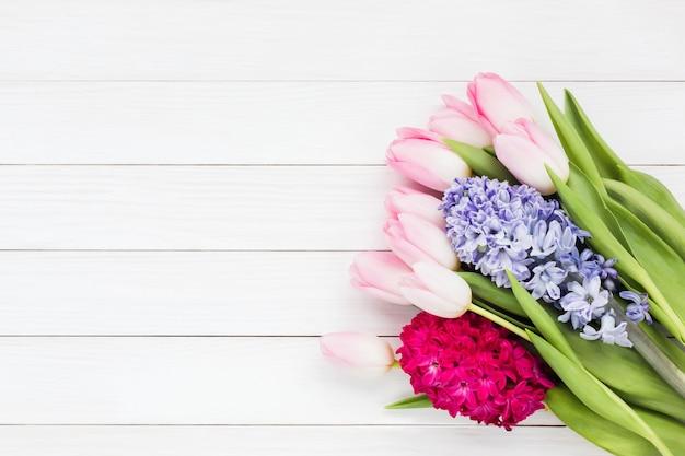 Copyspaceと白い木製の背景に春の花の花束。上面図