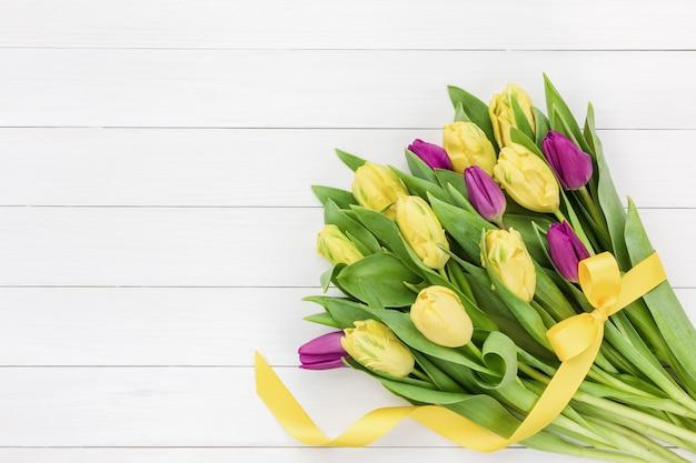 白い木製の背景に黄色のリボンと黄色とピンクのチューリップの花束。トップビュー、copyspace