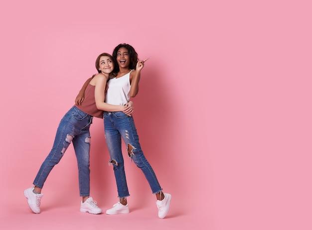 Портрет двух радостная молодая женщина, стоя с ее пальцем, указывая на розовый copyspace