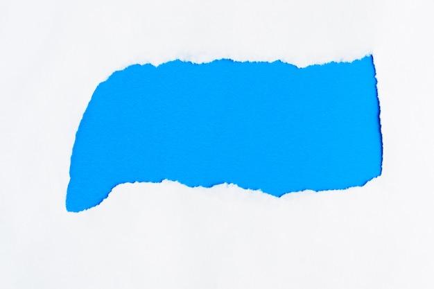 Разорванный белой бумаги на синем фоне copyspace для сообщения