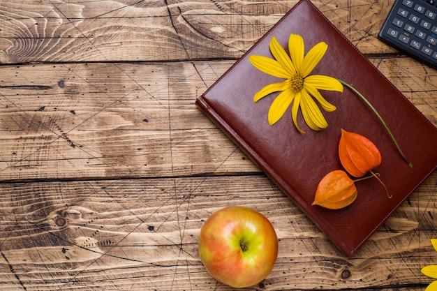 秋の花とcopyspaceの木製の背景上のテキストのメモ帳。