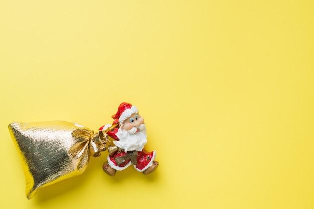 Copyspaceと黄色の贈り物の金の袋とおもちゃのサンタ。クリスマス新年のコンセプト。