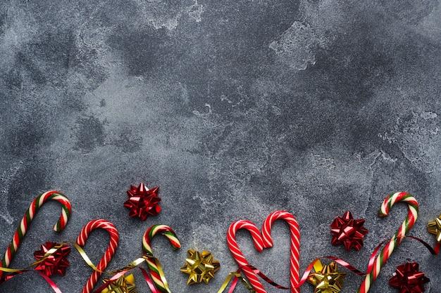暗い灰色のクリスマス杖キャラメルレッドゴールドの風景。 copyspaceフレーム。