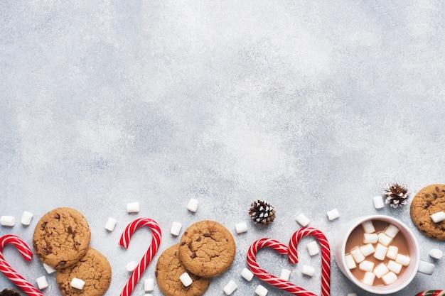 チョコレートチップクッキー、クリスマスの杖キャラメルカップココアとマシュマロコーングレーの装飾。 copyspaceフレーム。