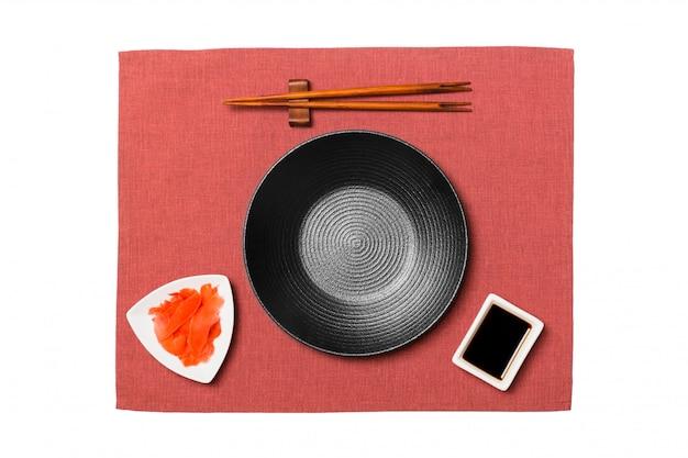 Пустой круглая черная тарелка с палочками для суши и соевый соус, имбирь на фоне красных салфеток. вид сверху с copyspace для вас