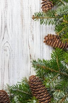 クリスマスの背景。木製のテーブルでモミの木の枝の松ぼっくり。平干し、copyspace