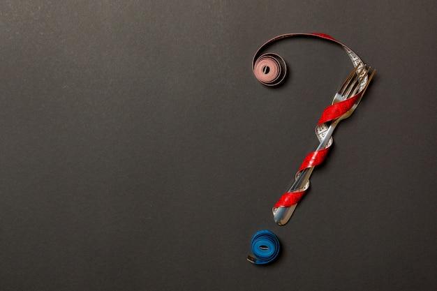 Взгляд сверху вопросительного знака сделанного из вилки и измеряя ленты на черноте. диета с copyspace