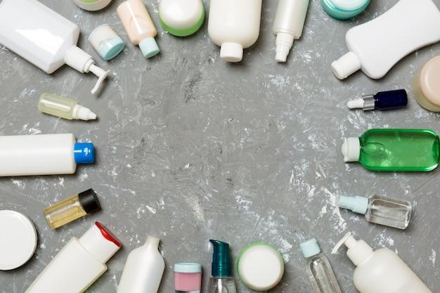 プラスチック製のボディケアボトルのフレーム緑の空のスペースに化粧品とフラットレイアウト構成。白い化粧品容器、copyspaceとトップビューのセット