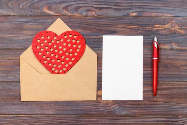 平らに置きます。上面図。聖バレンタインの日にラブレター。赤いハートの形をした手作りのポストカード。 copyspaceとバレンタインの日の概念