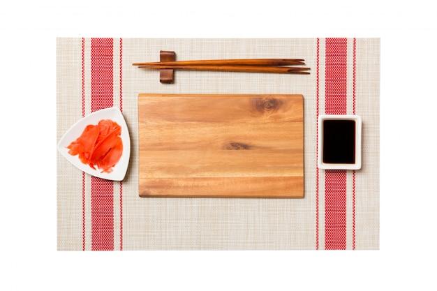 Пустая прямоугольная коричневая деревянная тарелка с палочками для суши, имбиря и соевого соуса на фоне суши мат. вид сверху с copyspace