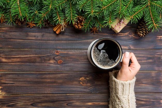 女性の手は、黒い木製のクリスマス背景にコーヒーのマグカップを保持します。トップビュー、copyspace