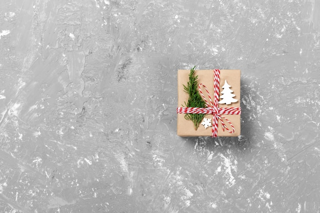Подарочная коробка, завернутая в переработанную бумагу, с бантиком из ленты, с рождественским декором. цементный стол фон, copyspace
