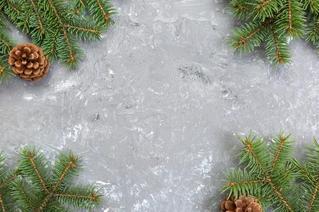 モミの木フレームとコーンcopyspaceとクリスマスグレーセメント木製の背景。トップビューの空きスペース