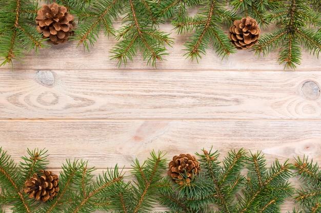 モミの木フレームとコーンcopyspaceとクリスマスグレーの木製の背景。トップビューの空きスペース