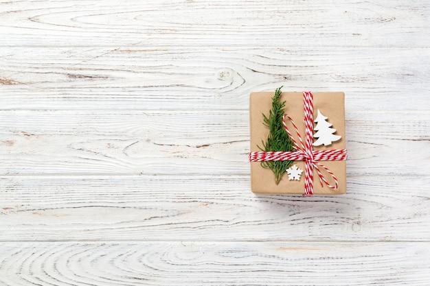 Подарочная коробка, завернутая в переработанную бумагу, с бантом из ленты, с рождественским декором. деревянный стол фон, copyspace