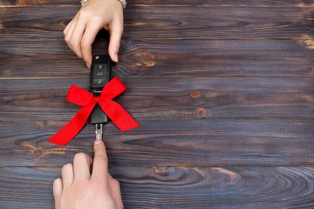 ウーメンは車の鍵を渡します。女性の手は赤い弓と車のキーを保持します。贈り物として車を贈る。 copyspace