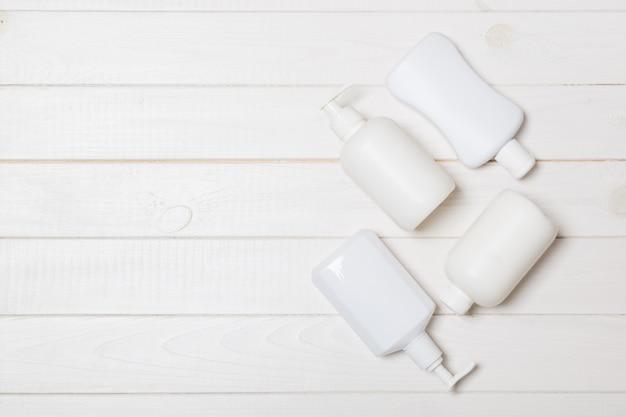 木製、トップビューcopyspaceに白い化粧品容器を設定します。グループのプラスチック製ボディケアボトル容器