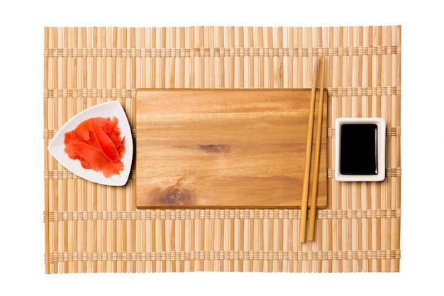 Пустые прямоугольные коричневые деревянные тарелки палочки для суши и соевый соус, имбирь на желтый бамбуковый коврик. вид сверху с copyspace
