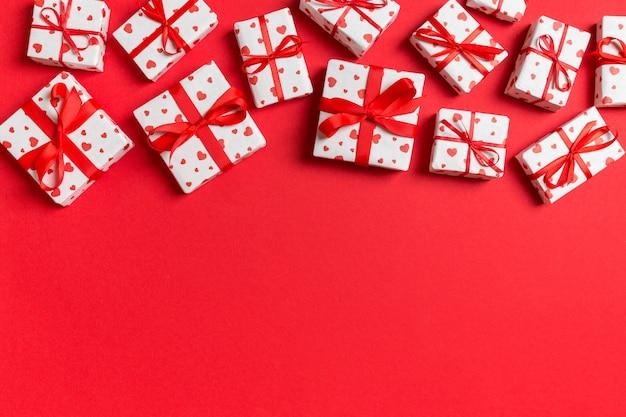 Copyspaceと赤の背景に赤いハートのギフトボックスの組成。バレンタインデーのコンセプトのトップビュー