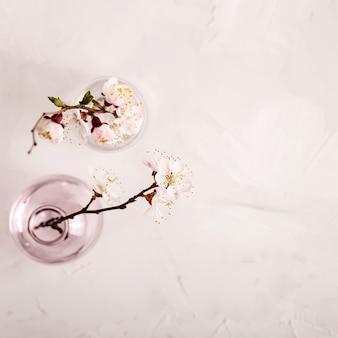 Copyspaceと枝に白い花を持つ春の中立的な光のミニマルな背景
