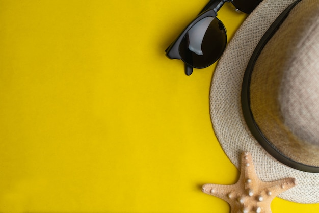 夏のアクセサリー、海の貝殻、帽子とサングラスcopyspaceと黄色の背景に。夏休みと海のコンセプト。