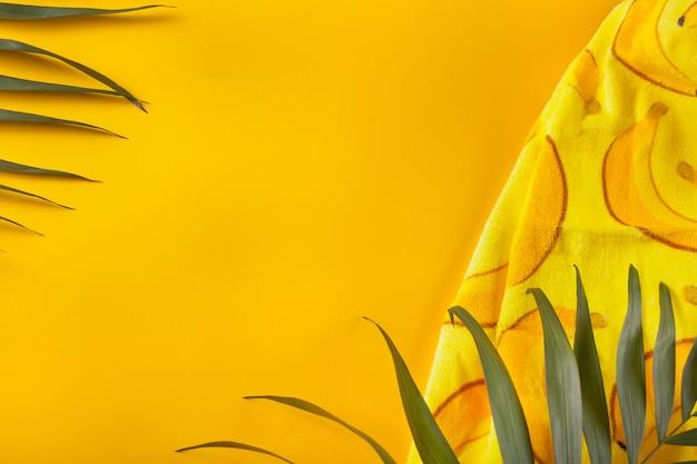 黄色の背景にビーチタオルと熱帯の葉。最小限の概念平らに置きます。 copyspace